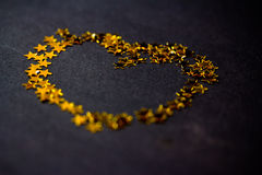 Golden heart made of stars on black Stock Images