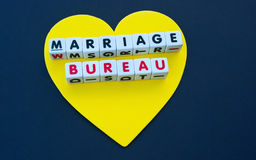 Golden heart marriage  bureau. A large gold / yellow  heart shape  on a black background with text 'marriage bureau' inscribed in uppercase letters on small Royalty Free Stock Photo