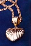 Golden heart necklace. Closeup over blue velvet background Stock Photo