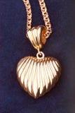 Golden heart necklace. Extreme closeup on blue velvet background Royalty Free Stock Photo