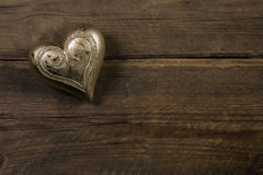 Golden heart on old wooden vintage background. Stock Image