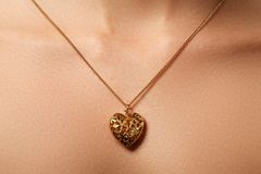 Golden heart pendant. Beauty and jewelry concept. Woman wearing Stock Photography