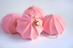 A golden heart pendant on pink strawberry meringues background Royalty Free Stock Photo
