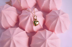 A golden heart pendant on pink strawberry meringues background Stock Photography