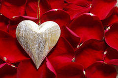 Golden heart on red rose petals Stock Images