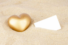 Golden heart in the sand with empty card Royalty Free Stock Photos