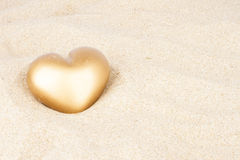 Golden heart in the sand. Golden valentine heart in the sand Royalty Free Stock Photo