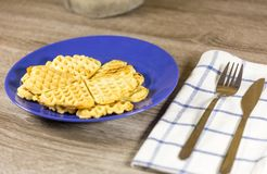 Golden heart shaped belgian waffles on blue plate. With napkin and cutlery on wooden table Royalty Free Stock Photography