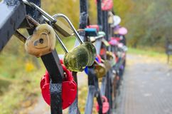 Golden heart-shaped padlock covered by drops of water in rainy autumn day. royalty free stock image