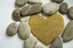Golden heart and stones on a white background stock image
