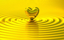 Golden heart touch making ripples. Golden heart over melted liquid gold and cause multiple waves. Metaphor of love, luxury, affection, mind, materialism and Stock Photography