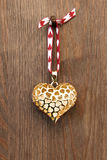 Golden heart on wooden background Stock Photo
