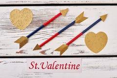 Golden hearts near arrows. Royalty Free Stock Photo