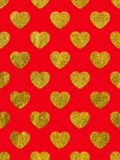 Golden hearts on a red background. Stock Photography