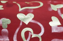 Golden hearts on red mesh Stock Photos