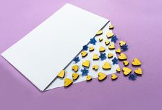 Golden hearts and small blue flowers in an envelope on a lilac background. Valentine`s Day. love concept Gift, message for lover. royalty free stock photography
