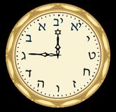 Golden hebrew clock with hebrew characters on clock face. Royalty Free Stock Photography