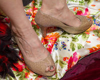 Golden high heel shoes turned almost 90 degrees at the ankles Royalty Free Stock Photography