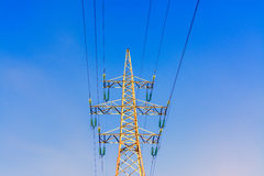 Golden high-voltage tower of against sky background. Steely golden color electric pylons and high voltage power lines of against the blue sky background Stock Image