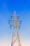 Golden high-voltage tower of against sky background. Royalty Free Stock Photography