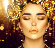 Golden holiday makeup. Golden wreath and necklace Stock Photo