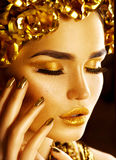 Golden holiday makeup. Golden wreath and necklace. Fashion art hairstyle, manicure and makeup Royalty Free Stock Image