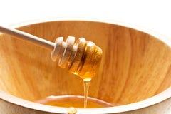 Golden honey in the bowl. Golden honey on the wooden honey dipper with bowl Stock Images