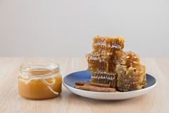 Golden honey in the comb in a jar and yellow sliced lemon Stock Photos