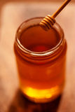 Golden Honey dipper and honey in jar on dark background close Stock Photos