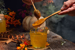 Golden honey drizzling onto wooden spoon in glass cup Stock Photos