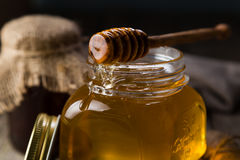 Golden honey in glass jar with dipper. Dark photo Royalty Free Stock Images