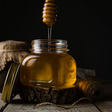 Golden honey in glass jar with dipper. Dark photo Royalty Free Stock Photography