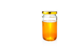 Golden honey in glass jar with lid on white background. Golden honey in glass jar with lid on isolated white background, room for copy space Royalty Free Stock Photos