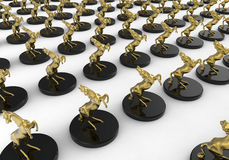 Golden horses award trophies. 3D render illustration of multiple golden horses award trophies. The composition is isolated on a white background with shadows Royalty Free Stock Images