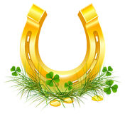 Golden Horseshoe and coins on grass clover. Patricks Day symbols Stock Photos