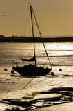 The Golden Hour. A lone yacht sits on the estuary waiting for the tide to float Stock Photos