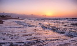 Golden hour on the beach. Sunrise on the beach, capturing all the typical colorful of the golden hour in the Mediterranean Sea, appreciating in the background a Royalty Free Stock Images