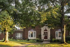 Golden Hour on the maple trees in front of traditional brick house with columns and bay windows - light stretching across front ya. Rd and up tree trunks stock photos