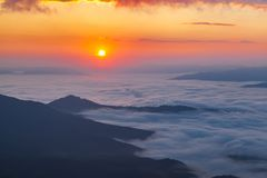 Golden hour in the mountains. Aerial view from top of a hill at the beautiful red sunrise in golden hour over the mountains and foggy valley like the sea stock image