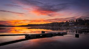 Golden hour of pier under beautiful sky. With reflection on the sea, Fornebu, Norway royalty free stock photography