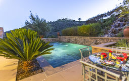 Golden hour pool and eating area luxury home San Diego County Royalty Free Stock Image