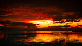Golden hour. After the rain sunset skies overlooking the docks of a small fishing boat harbor Stock Image