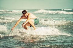 Golden hour skimboarding. Ocean. Young man rides the waves Royalty Free Stock Photography