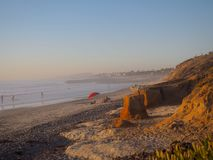 Golden Hour Sunset on the Pacific Ocean in Southern California. The golden hour of sunset on the Pacific coast in Carlsbad, California. A red umbrella stands out royalty free stock images