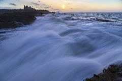 Golden hour, Tantallon castle with rough seas and huge waves Royalty Free Stock Image
