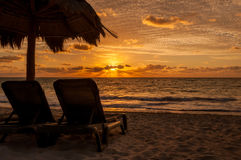 Golden Hour. Two empty beach lounge chairs viewing a golden sunrise on Riviera Maya Royalty Free Stock Image