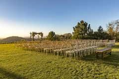 Golden hour of the wedding seating area from back with wider cro. P. Wonderful seating arrangement of an outdoor wedding in southern California. Flowers and Royalty Free Stock Photo