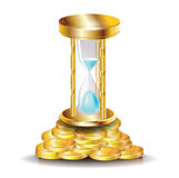 Golden hourglass on pile of coins Stock Photo
