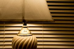 Golden hue of a lamp. With window blinds in the background Stock Image