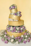 Golden Icing Wedding Cake - White and Purple Roses Stock Photo
